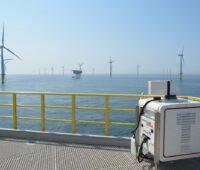 Zu sehen ist ein Lasergerät mitten im Offshore-Windpark, mit dessen Hilfe die Leistung von Offshore-Windparks exakter vorhersehbar werden soll.