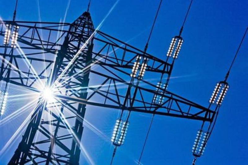 Die Sonne strahlt bei blauem Himmel durch das Gerüst eines Strommastes