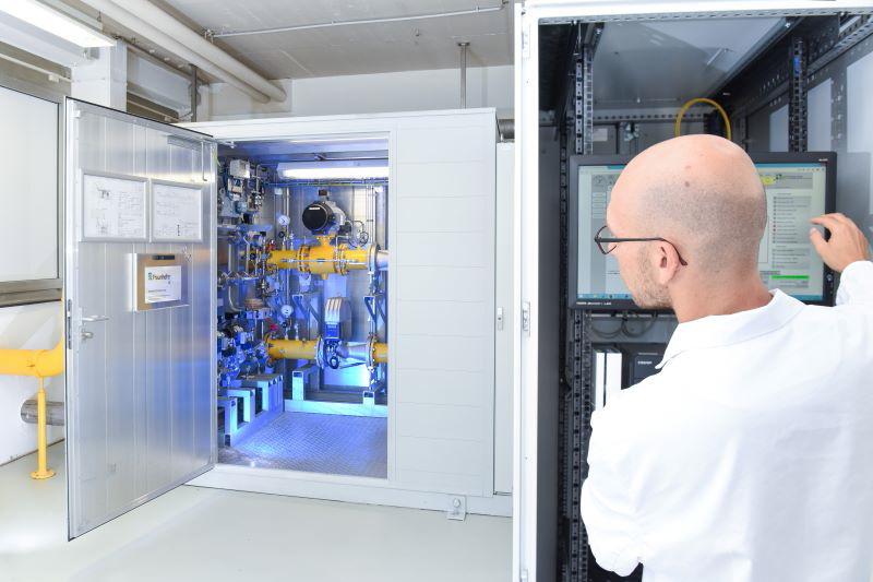 Ein Forscher im weißen Kittel blickt im Labor in einer Wasserstoff-Pilotanlage