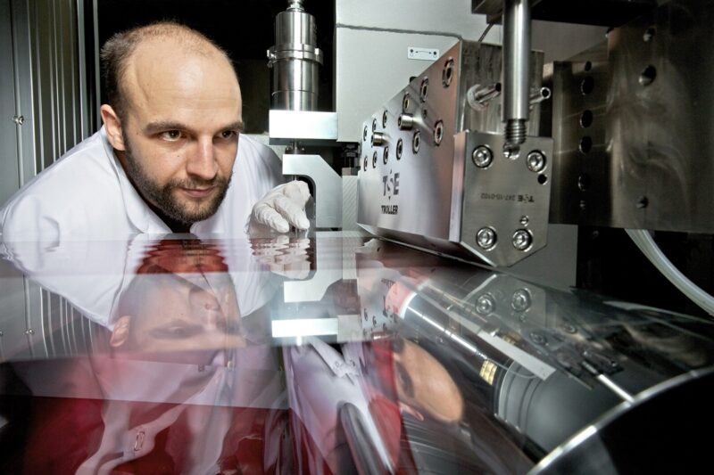 Das Bild zeigt einen Wissenschaftler der die Rolle-zu-Rolle-Anlage für die Produktion von Membranen für Brennstoffzellen betrachtet.