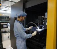Ein Laborant hält eine Solarzelle vor einer Maschine in der Hand.