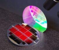 Zu sehen ist die Tandem-Photovoltaik. Die oberste Teilzelle leuchtet rot.. Die nanostrukturierte Rückseite schimmert in Regenbogenfarben.