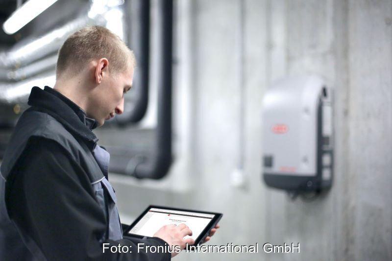 Ein Techniker blickt vor dem Hintergrund eines Wechselrichters an der Wand auf ein Tablet.