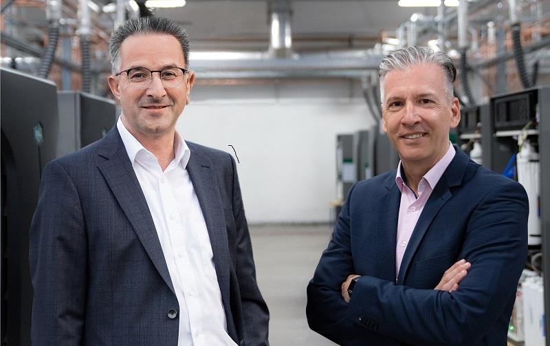 Zu sehen sind Jörn Hedtke, Verkaufsleiter Heizung der GC Gruppe und Matthias G. Adler, CSO der Solidpower Gruppe, die eine Kooperation zum Vertrieb vom Brennstoffzellengerät Bluegen vereinbart haben.