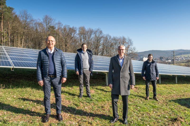 Vier Personen auf grüner hügeliger Wiese mit Photovoltaik .