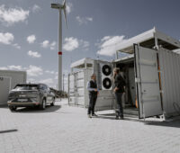 Rechts ein Container mit technischen Anlagen, im Hintergrund eine Windkaftanlage. Vor dem geöffneten Container stehen zwei Menschen. Ein Auto parkt vor einem weiteren Container.