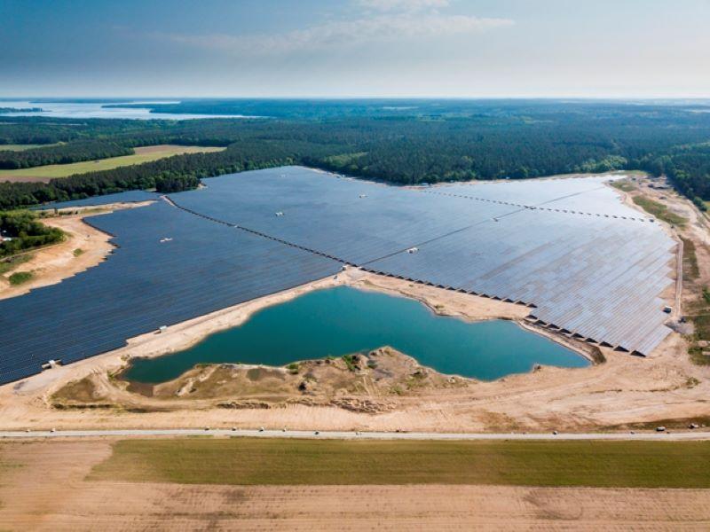 Luftaufnahme eines großen PV-Parks mit angrenzendem See einer Kiesgrube.