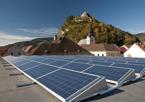 Foto einer PV-Anlage auf einem Flachdach. Im Hintergrund ein Österreichisches Dorf und Berge.
