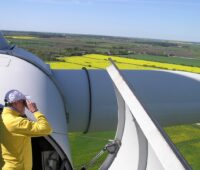 Zu sehen ist eine Person auf einer Gondel einer Windenergie-Anlage, hier sind die Mindestabstände eingehalten.