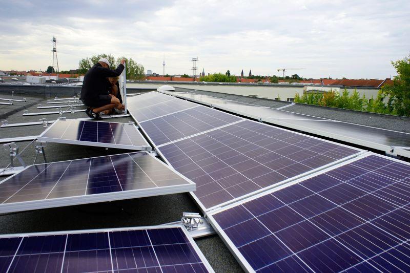 Monteure befestigen Solarmodule auf einem Flachdach. eines hohen Gebäudes.