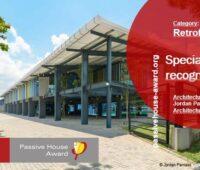 Foto eines Gebäudes mit grafischen Elementen, die auf die Auszeichnung verweisen, Passivhaus-Fabrik Sri Lanka