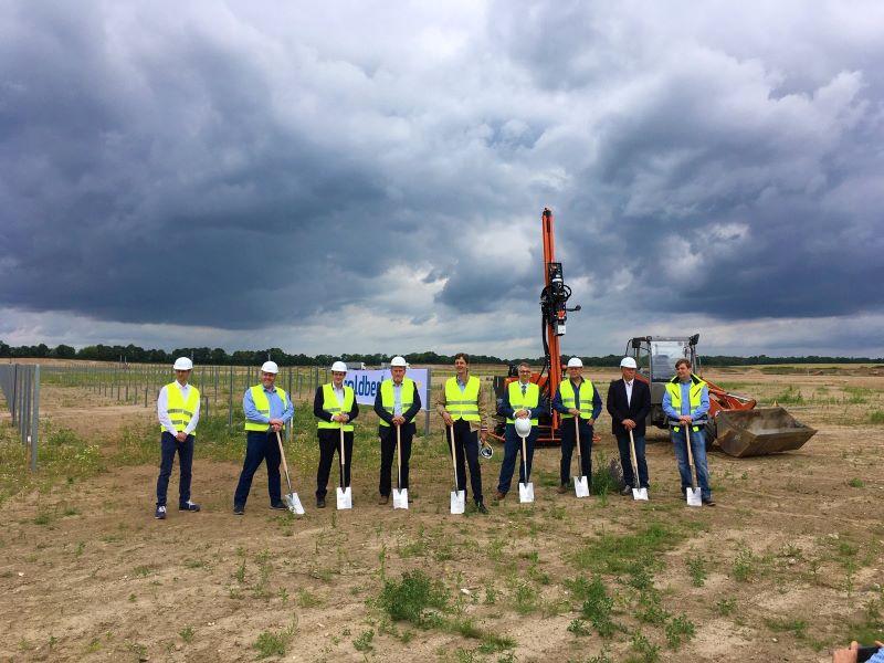 Auf einer planierten Fläche stehen neun Männer mit Sicherwesten udn Spaten vor einem Baufahrzeug