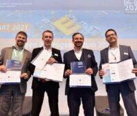 Vorstellung des Wasserstoff-Manifest: Vier Männer mit Papieren in der Hand auf einer Bühne vor einer Leinwand.