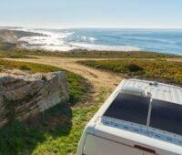Ein Caravan mit Solarzellen an einer Küstenlandschaft mit Meer.