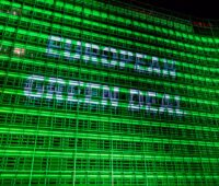 "Fassade des Berlaymont-Gebäudes in Brüssel, nachts illuminiert mit der Schriftzug ""Green New Deal"""