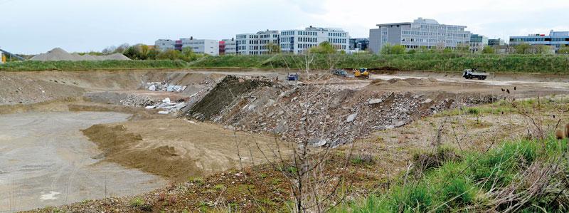 Im Vordergrund eine Kiesgrube, im Hintergrund eine Siedlung