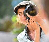 """Zu sehen ist eine Fotografin, die durhc ihre Kamera schaut. Findet sie ein Motiv für den Fotowettbewerb """"Fokus Energiewende - Deine Welt, dein Bild""""?"""