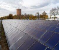 Einige Reihen mit blauen Solarwärmekollektoren. Im Hintergrund ein alter Wasserturm aus Backsteinen.