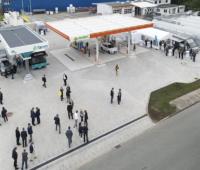Luftaufnahme über zwei Tankstellen-Dächer und Menschen mit dunklen Anzügen - Einweihungsfeier für die Wasserstofftankstelle