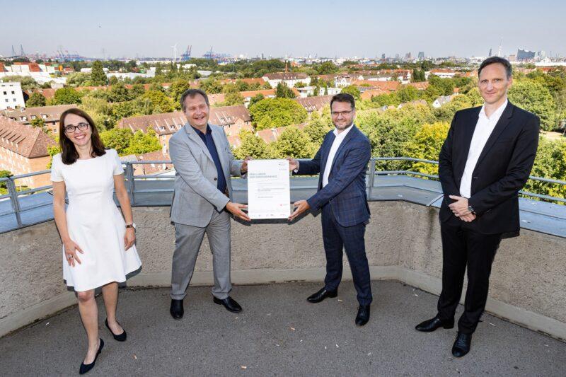 """Zu sehen ist die Übergabe des Förderbescheids für das Reallabor """"Integrierte WärmeWende Wilhelmsburg IW3"""" mit Vertretern aus Politik und Wirtschaft."""