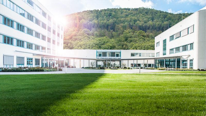 Geschäftsgebäude mit Wiese im Vordergrund und bewaldetem Berg im HIntergrund