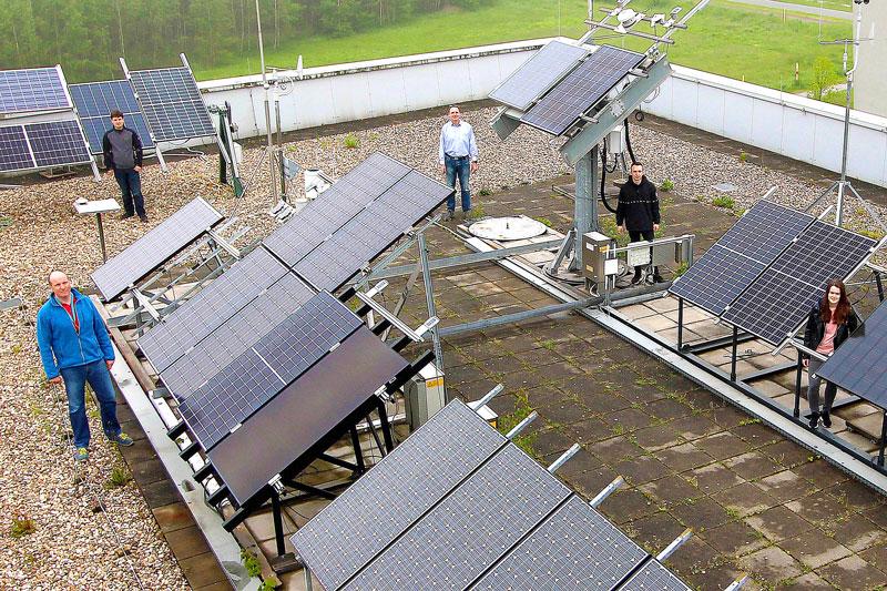 Fünf Mitarbeiter:innen präsentieren Photovoltaik-Teststand auf einem Dach der Hochschule Gelsenkirchen, wo auch bifaziale PV-Module getestet werden.