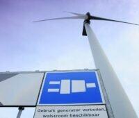 Zu sehen ist eine Windkraftanlage und ein Hinweisschild zur Landstromanlage mit Windenergie im Rotterdamer Hafen.
