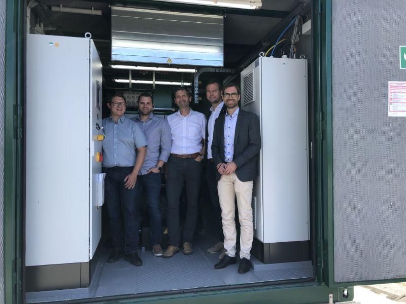 Fünf Männer stehen in einem Container für ein Wasserstoff-BHKW