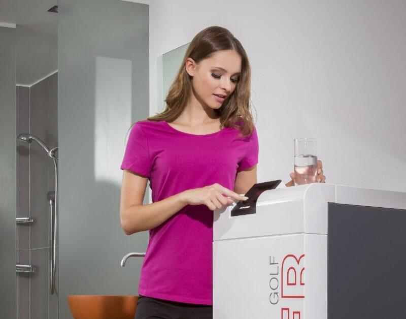 Zu sehen ist eine Frau im Badezimmer, wo sich die Heizung mit Geothermie befindet.