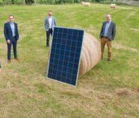 Zu sehen ist das Team von Highfield Solar auf einem Acker mit Photovoltaik-Modul.