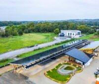 Luftbild eines Ladeparks für E-Autos, überdacht mit PV-Anlagen.
