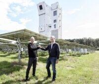 Zu sehen sind Helikon-Geschäftsführer Patrick Hilger und Synhelion-CEO Gianluca Ambrosetti in einem CSP-Spiegelfeld für hochkonzentrierende Solartechnologie mit dem Solarturm im Hintergrund.
