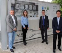 Zu sehen sind die Projektverantwortlichen vor einer Redox-Flow-Batterie, einem Teil der geplanten Hybrid-Energiespeicher.