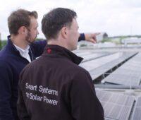 Zu sehen sind zwei Menschen auf einem Hallendach mit Photovoltaik als Sinnbild für die Abteilung Commercial Energy Systems.