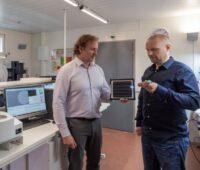 Drei Mä#nner stehen in einem Labor mit Messgeräten. Einer präsentiert eine schwarze Solarfolie.
