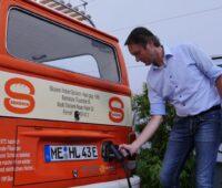 Ein Mann lädt seinen alten VW Bulli mit Strom.