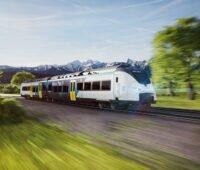 ein Zug mit Bayern-Logo vor einer Berglandschaft