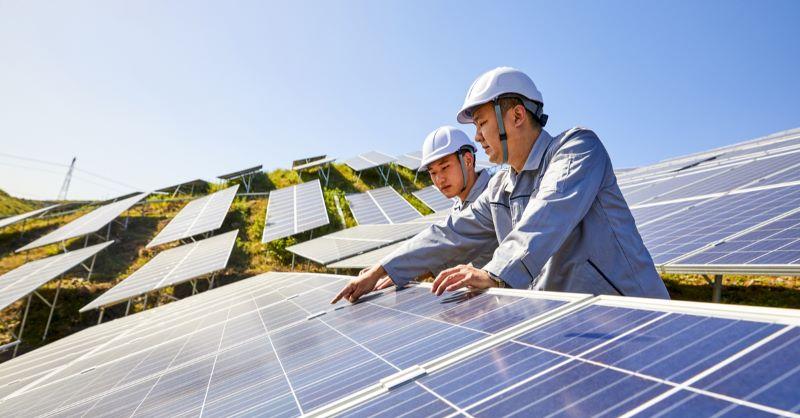 Zwei asiatische Projektentwickler in einer Photovoltaikanlage,