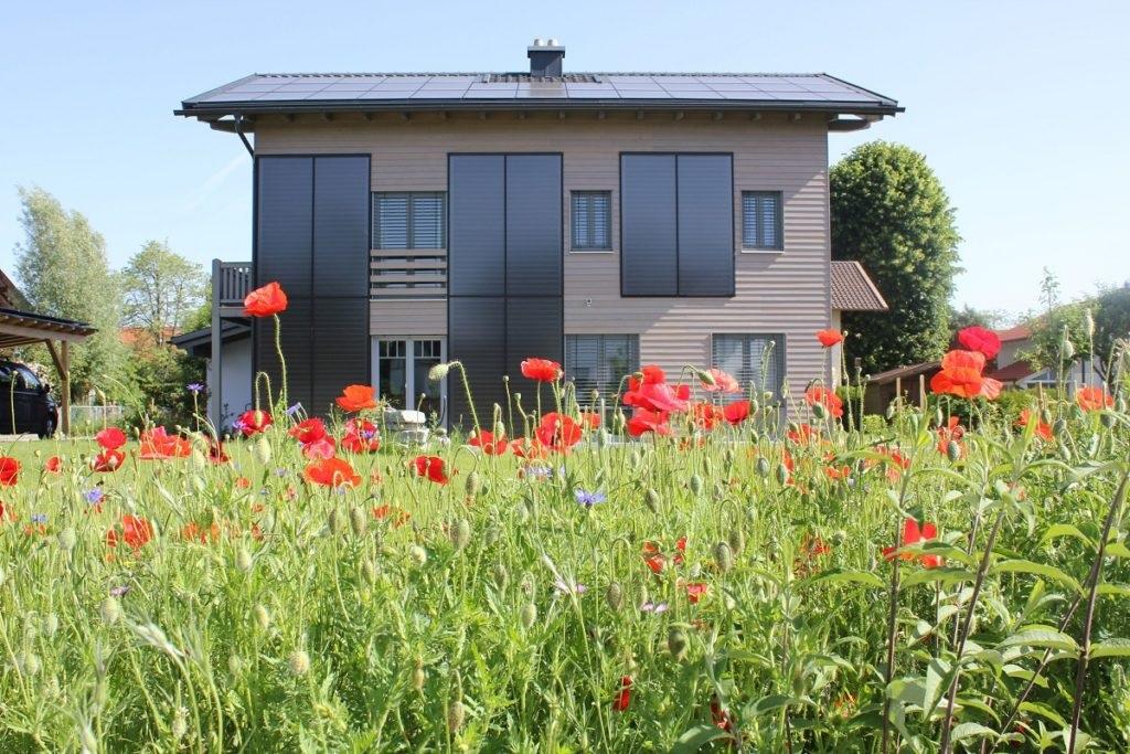 Zu sehen sind Solarthermie Kollektoren einer Solarheizung, die an der Fassade eines Hauses montiert sind.