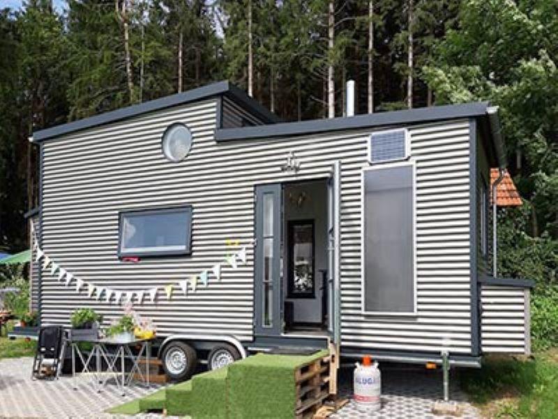Ein kleines silberfarbenes mobiles Haus auf einem PkW-Anhänger