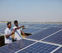 Zwei Männer in einem großen Solarpark in Indien.