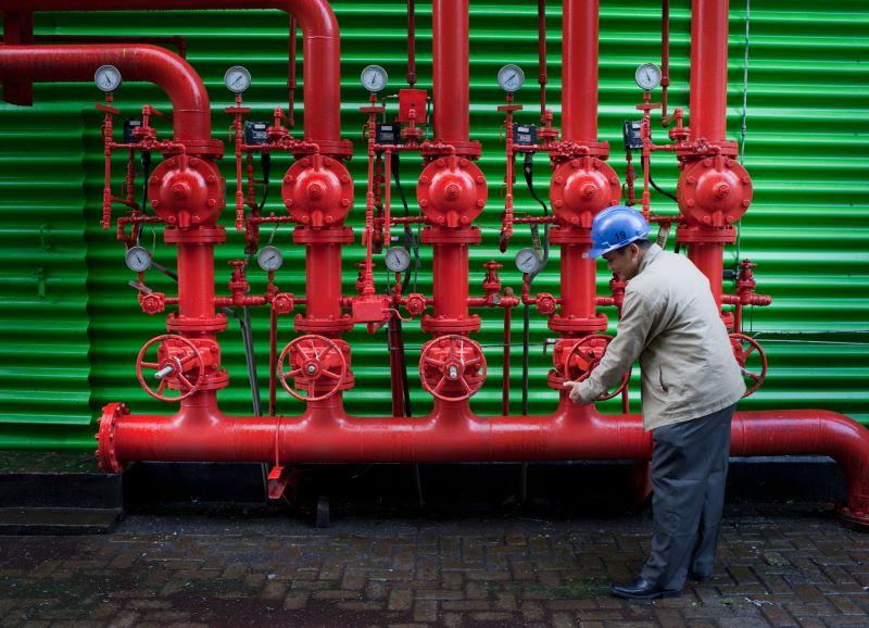 Ein Arbeiter an einem Schaufelrad mit rotem Rohrsystem.