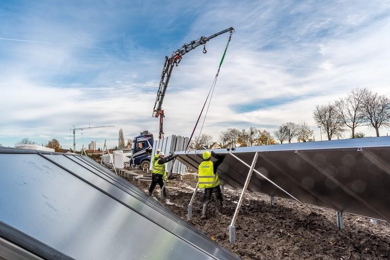 Monteure in gelben Westen installieren große Solarwärmeanlagen. Dabei hilft ein Kran, der im Hintergrund agiert.