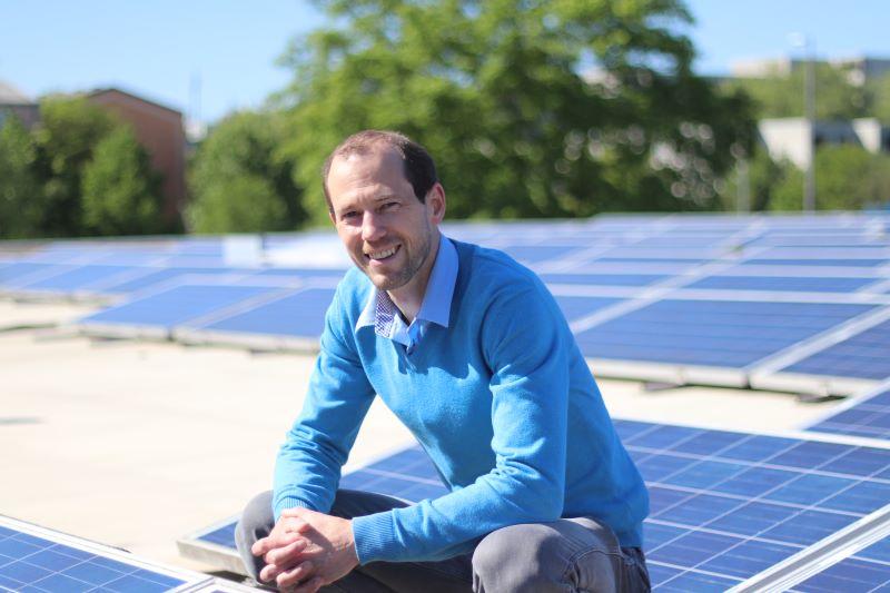 Installation-Gründer Meyer-Delpho lachend auf einem Dach mit Solarmodulen.