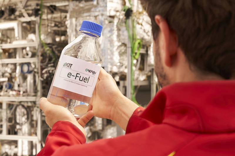 Zu sehen ist ein Mann, der eine Flasche mit dem synthetischen Kraftstoff hält, das in der PtX-Anlage erzeugt wurde, die das Spin-off Ineratec mit und an dem KIT entwickelt hat.