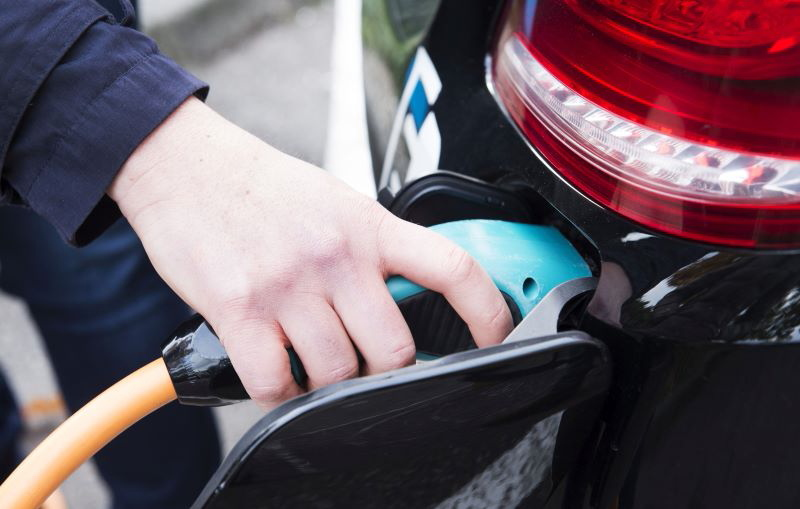 Eine Hand am Stecker beim Laden des E-Autos.