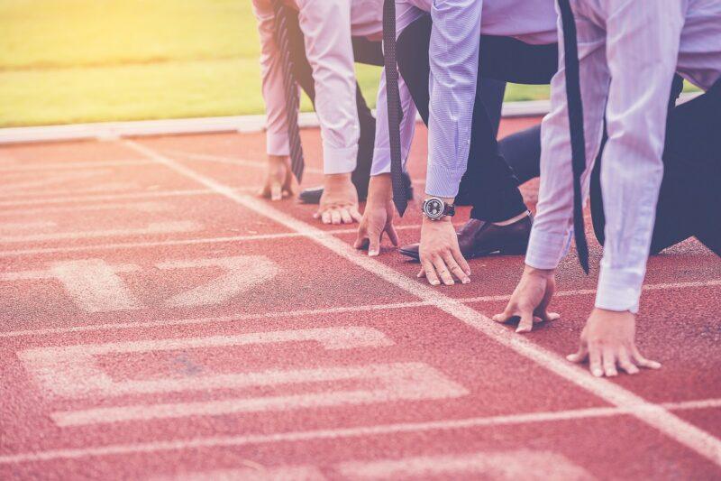 Zu sehen sind Personen in Startposition auf der Laufbahn als Symbol für den KUER.NRW Gründungswettbewerb KUER.NRW Gründungswettbewerb.