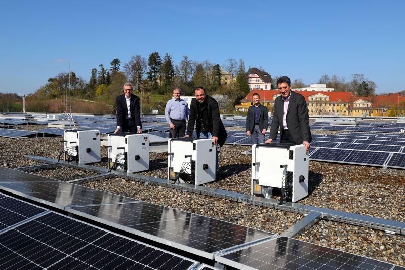 Mehere Personen freuen sich auf dem Flachdach eines Gebäudes über eine dort installierte PV-Anlage.