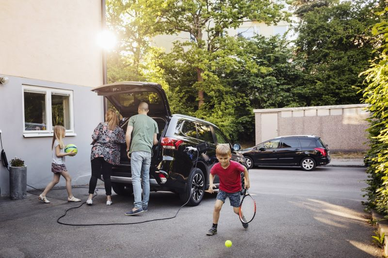 Eine Familie packt ihr Elektroauto, das gerade geladen wird.
