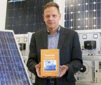 Zu sehen ist Prof. Dr. Konrad Mertens mit seinem Photovoltaik-Lehrbuch.